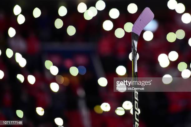 Washington Capitals player holds up a stick with lavender tape during a NHL-wide moment of silence for Hockey Fights Cancer before a game between the...