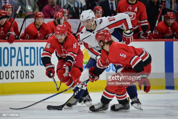 Washington Capitals Right Wing Brett Connolly is sandwiched between Carolina Hurricanes Center Marcus Kruger and Carolina Hurricanes Defenceman Noah...
