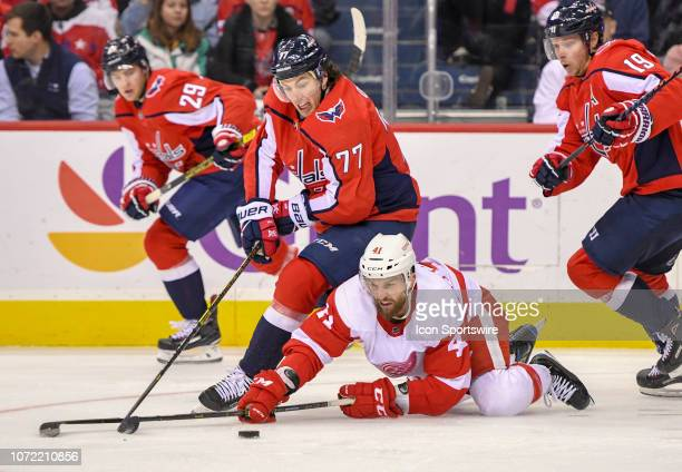 Washington Capitals right wing TJ Oshie fights for a loose puck with Detroit Red Wings center Luke Glendening on December 11 at the Capital One Arena...