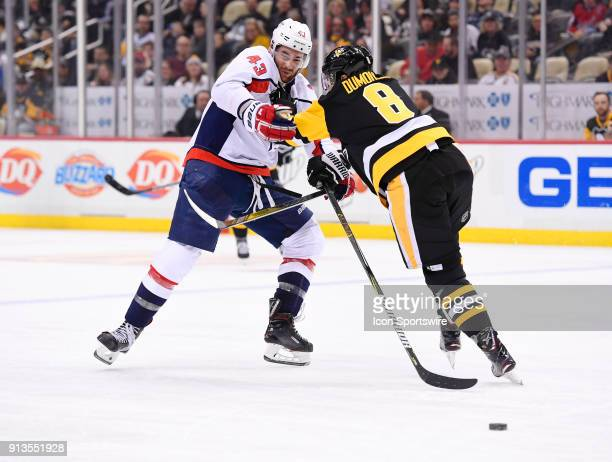 Washington Capitals Right Wing Tom Wilson is checked by Pittsburgh Penguins Defenseman Brian Dumoulin as he goes for the puck during the third period...