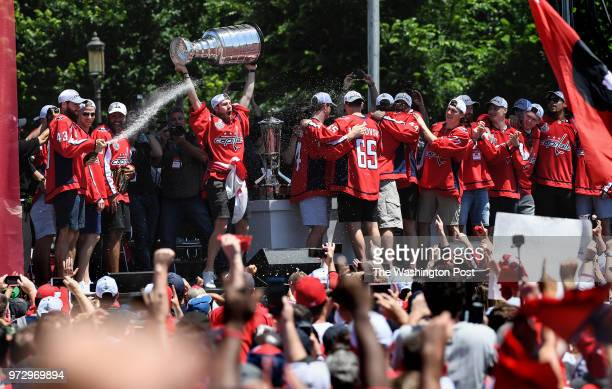 WASHINGTON DC JUNE Washington Capitals right wing Tom Wilson sprays the crowd with a beverage as Washington Capitals goaltender Philipp Grubauer...