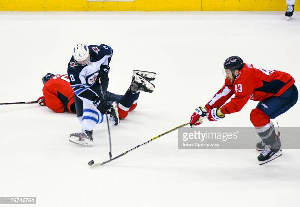 Washington Capitals right wing Tom Wilson takes the puck away from Winnipeg Jets defenseman Jacob Trouba in the third period on March 10 at the...