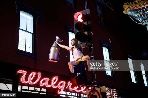 A Washington Capitols fan sits on a traffic signal while celebrating after the Washington Capitals won Game 5 of the Stanley Cup final against the...