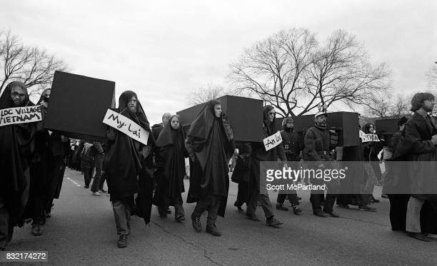 Hundreds of young activists dressed in black and wearing signs of protest around their necks march in Washington DC protesting the Vietnam War and...