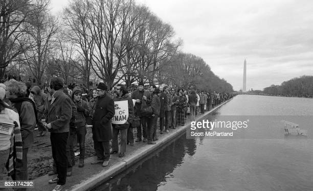 Large groups of activists line up next to the Lincoln Memorial Reflecting Pool in Washington DC in protest of the Vietnam War and Richard Nixon's 2nd...