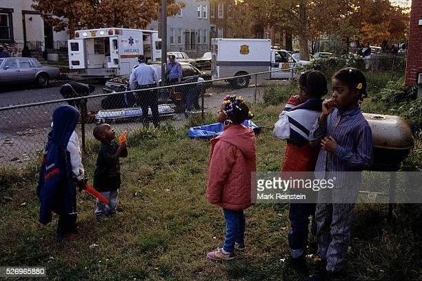 Washington, DC. 1993 Children in DC. Watch as paramedics work on a drug overdose victim on sidewalk in from of their home. Credit: Mark Reinstein
