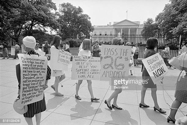 A women's group called NOW for National Organization for Women pickets the White House protesting discrimination against women Wearing flower...