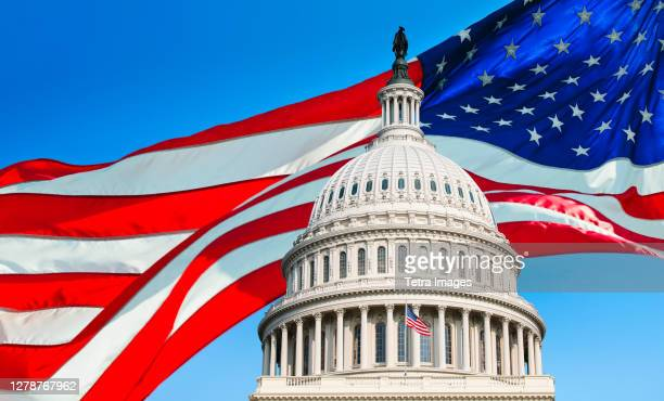 usa, washington d.c., capitol building against background of american flag - capitol hill stock pictures, royalty-free photos & images
