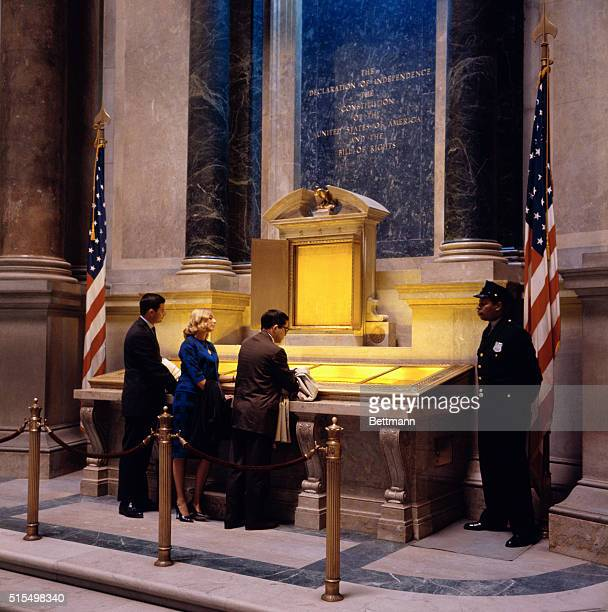In the exhibition hall of the National Archives a guard keeps watch while visitors study the following script of the Constitution and Declaration of...