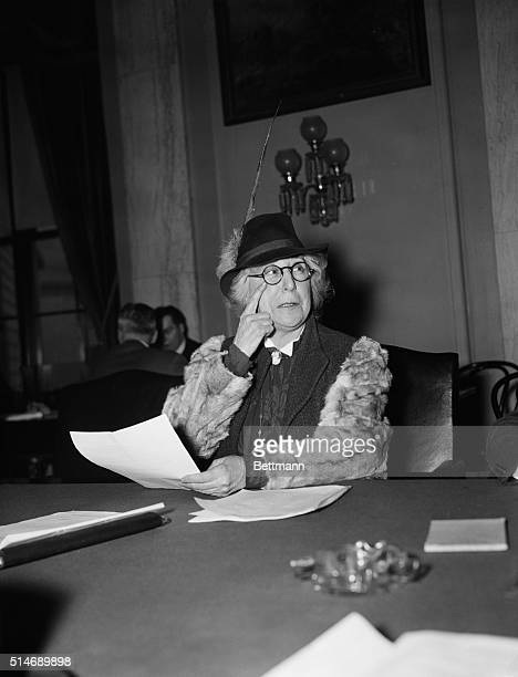 Washington, DC: Jeanette Rankin, before Senate Naval Affairs Committee. Miss Rankin is wearing a jaunty hat with a feather and is pointing at her eye.