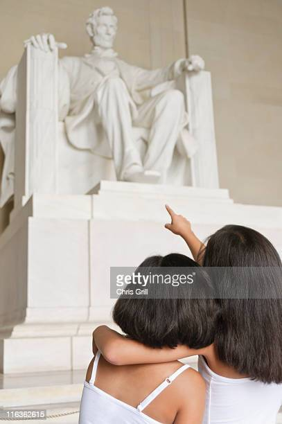 usa, washington dc, lincoln memorial, two girls (10-11] looking at lincoln statue - family politics stock pictures, royalty-free photos & images