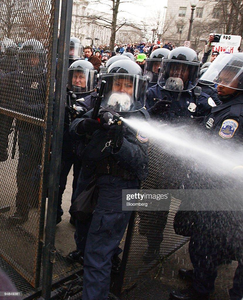 A Washington D C  police officer pepper sprays demonstrators