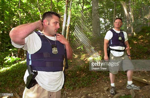 Washington, DC police officers John Hansohn, right, and Mark Saunders check in as they search for missing inter Chandra Levy in Walter Pierce Park...
