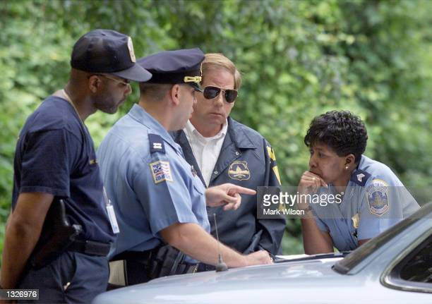 Washington DC police officials converse before searching Rock Creek Park for missing intern Chandra Levy July 16 2001 in Washington DC