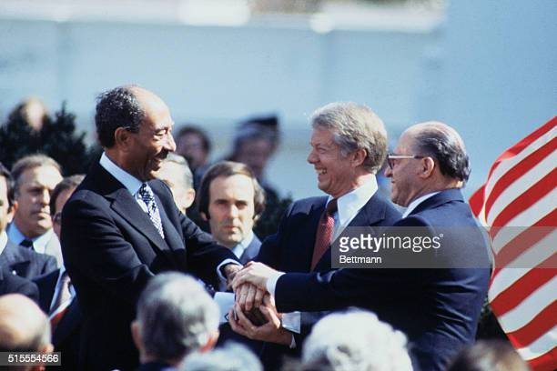 President Carter Anwar Sadat and Menachem Begin in three way handshake after signing of peace treaty