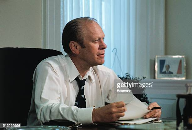 President Gerald Ford sits at his desk in the White House and works on the speech he will deliver to the nation by TV tonight telling the people...