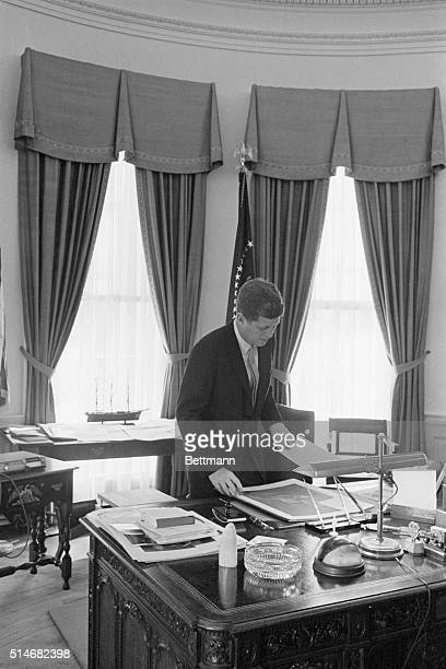 3/25/1961 Washington DC President John F Kennedy lives on his feet standing more during the day than sitting Here Kennedy examines a picture...