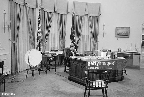 President Kennedy is shown talking on the phone in his office in the White House