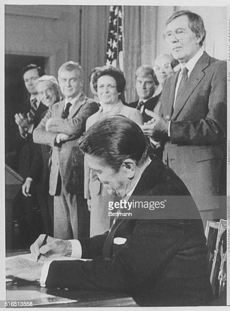 President Reagan signs the Atomic Energy Act Amendments in the Senate dining room of the White House Shown behind Reagan are Sen John Heinz RPa Rep...