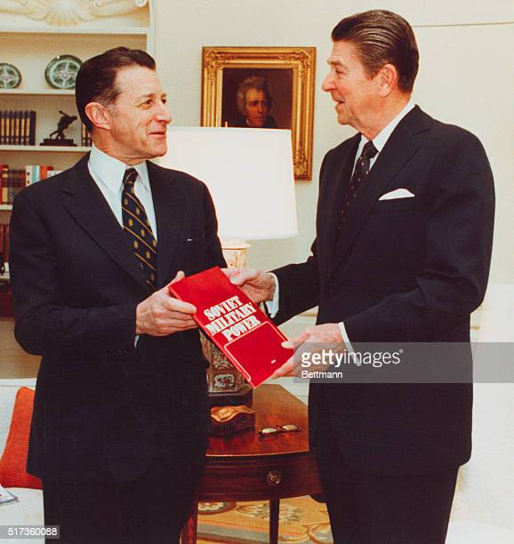 President Ronald Reagan receives a booklet entitled Soviet Military Power from Secretary of Defense Caspar Weinberger today in the Oval Office The...