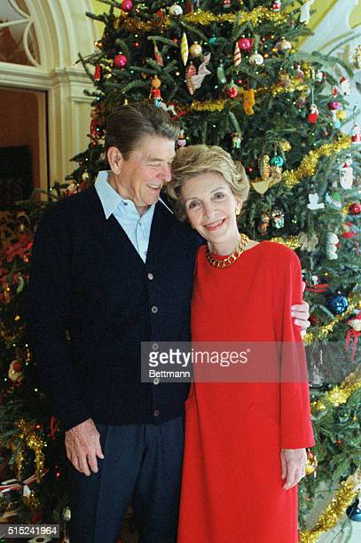 Their arms around each other President and Mrs Reagan pose in front of the family Christmas tree December 24 The president is in casual attire while...