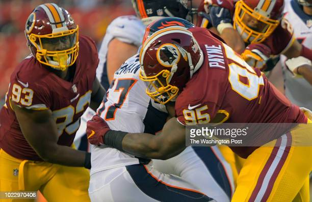 Washington defensive tackle Da'Ron Payne right brings down Denver running back Royce Freeman as Washington defensive end Jonathan Allen closes in...