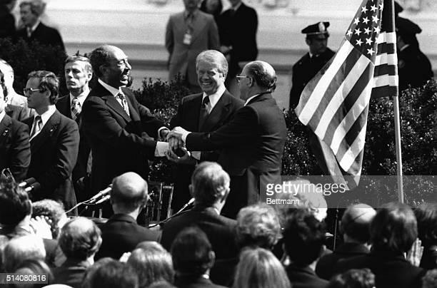 Egyptian President Anwar Sadat President Jimmy Carter and Israeli Prime Minister Menachem Begin congratulate one another in a threeway handshake...