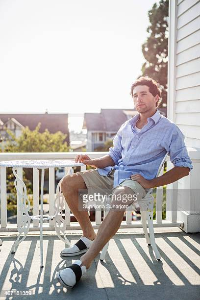 USA, Washington, Everett, Portrait of young man relaxing on balcony