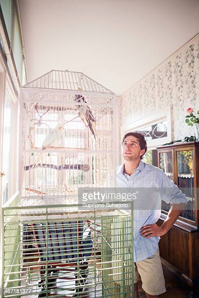 USA, Washington, Everett, Portrait of young man standing by bird cage and looking at parrot