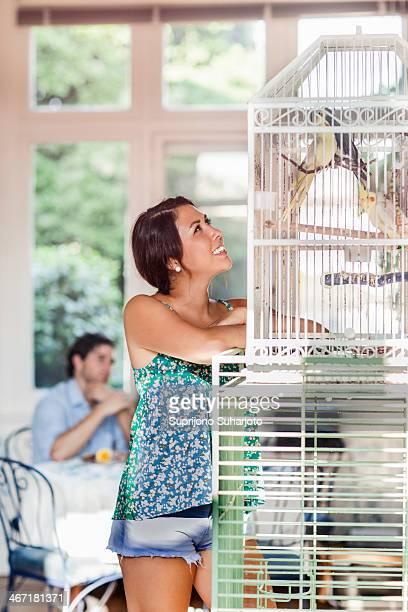 USA, Washington, Everett, Woman standing by bird cage, man in background