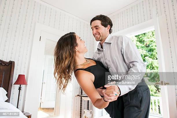 USA, Washington, Everett, Young couple dancing in bedroom