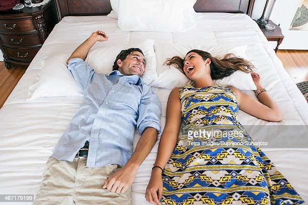 USA, Washington, Everett, Young couple lying on bad in hotel room