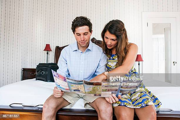 USA, Washington, Everett, Young couple sitting on bed in hotel room and reading brochure