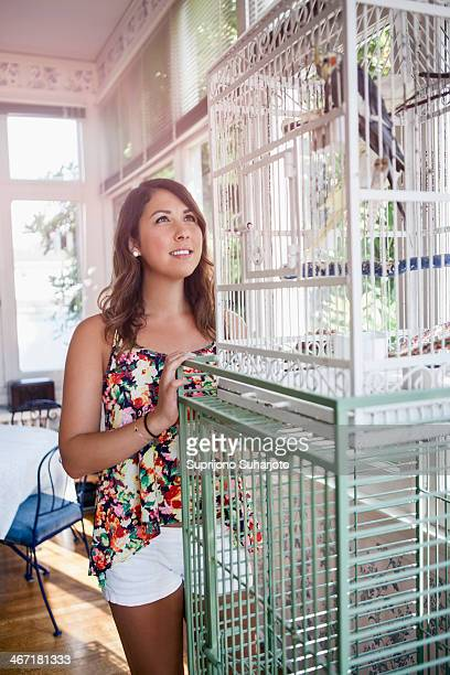 USA, Washington, Everett, Young woman watching bird in birdcage