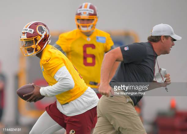 Washington first round draft pick quarterback Dwayne Haskins Jr left rolls out as QB Josh Woodrum center watches and head coach Jay Gruden runs past...