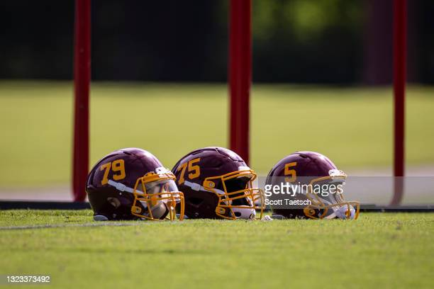 Washington Football Team helmets are seen on the field during mandatory minicamp at Inova Sports Performance Center on June 10, 2021 in Ashburn,...
