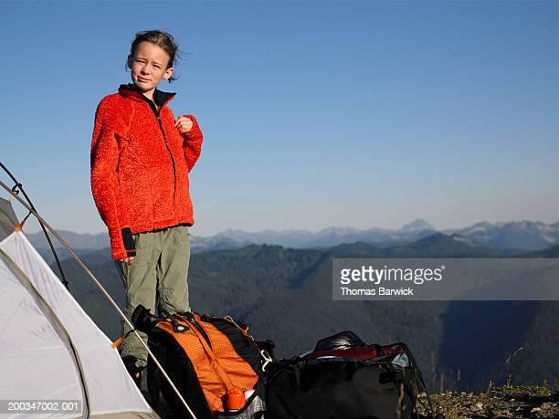 USA, Washington, girl (9-11) standing beside tent on mountaintop