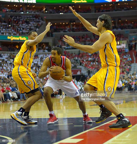 Washington guard Andre Miller drives between Indiana forward Evan Turner and Indiana forward Luis Scola in the first half as the Washington Wizards...