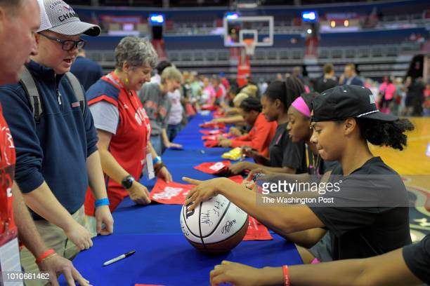 Washington guard Kristi Toliver right signs a basketball along with her other teammates at a long table on the floor after their game got canceled...