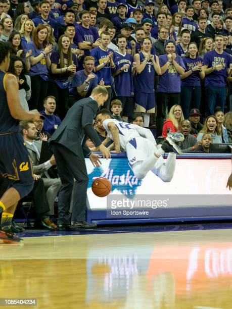 Washington Huskies forward Dominic Green slams into the announcer table during a college basketball game between the California Golden Bears against...