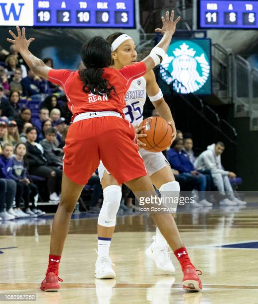 Washington Huskies guard Alexis Griggsby passes the ball against Utah Utes guard Erika Bean during a college basketball game between the Utah Utes...