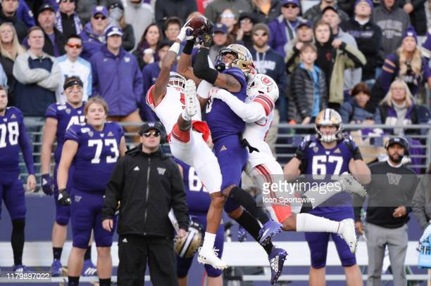 Washington Huskies wide receiver Marquis Spiker , Utah Utes defensive back Tareke Lewis and defensive back Julian Blackmon go up for a ball during a...