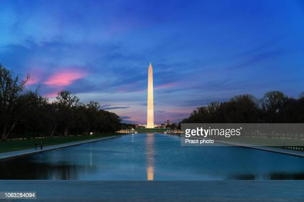 washington monument with lake at night with dramatic clouds in washington dc, usa. - washington monument washington dc stock pictures, royalty-free photos & images