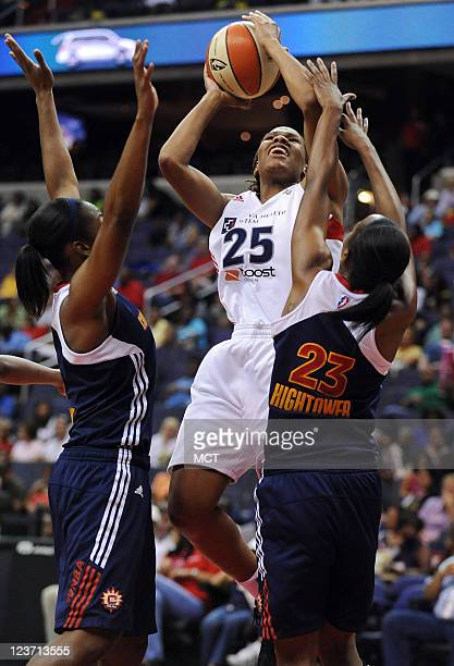 Washington Mystics forward Monique Currie goes up for a score between Connecticut Sun guards Allison Hightower and Danielle McCray left during the...