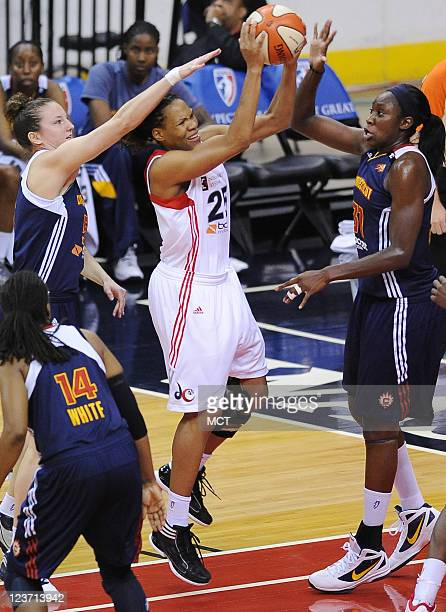 Washington Mystics forward Monique Currie takes the ball up against Connecticut Sun forward Kelsey Griffin left and Sun center Tina Charles during...