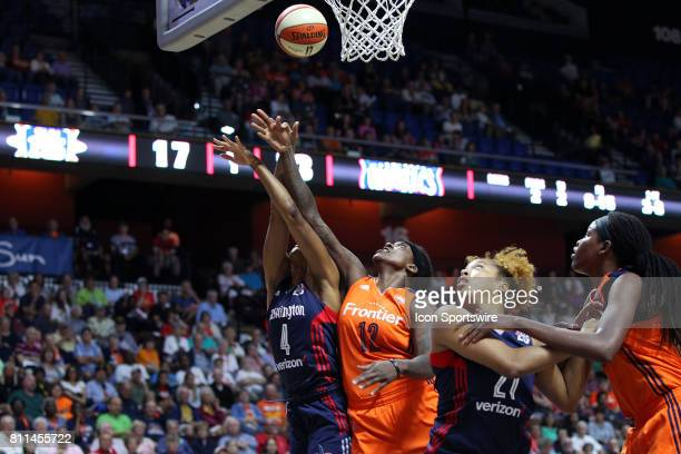 Washington Mystics guard Tayler Hill and Connecticut Sun center Lynetta Kizer battle for the rebound during the first half of an WNBA game between...