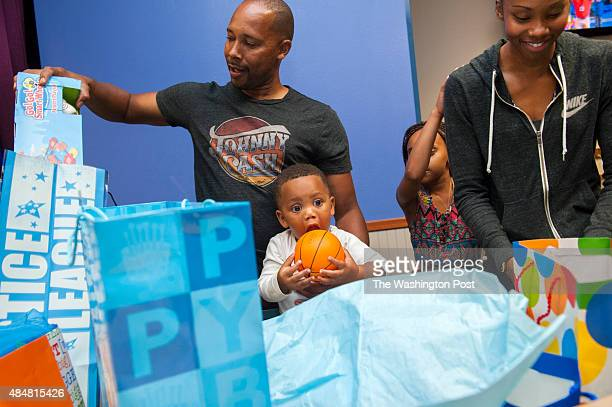 Washington Mystics guard Tayler Hill right and her father Paul Hill help Tayler's son Maurice open belated first birthday presents at Chuck E...