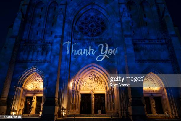 Washington National Cathedral is illuminated in blue with the words Thank You projected on the facade as a tribute to healthcare workers responding...