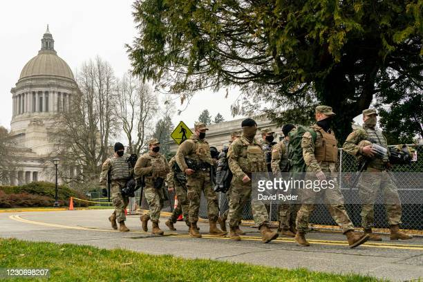 Washington National Guard personnel walk on the Washington State Capitol campus on January 20, 2021 in Olympia, United States. One Donald Trump...