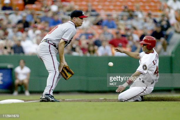 Washington Nationals' Alex Escobar slides into third as Chipper Jones of the Atlanta Braves receives the late throw in the second inning at RFK...
